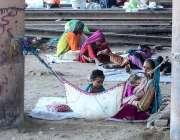 حیدر آباد: خانہ بدوش خاتون اپنے بچے کو جھولا دے رہی ہے۔