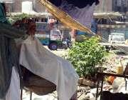 راولپنڈی: شہری سڑک کنارے حجام سے بال کٹوا رہا ہے۔