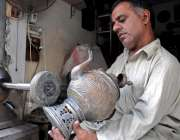 راولپنڈی: کاریگر پرانے برتنوں کو فروخت کے لیے گلی کر رہا ہے۔