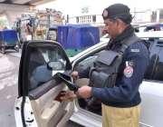 پشاور: کینٹ ریلوے اسٹیشن کے سامنے پولیس اہلکار کار سے کالا اسٹیکر ہٹاتے ..