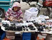 لاہور: محنت کش خاتون سڑک کنارے عینکیں فروخت کرنے کیلئے بیٹھی ہے۔