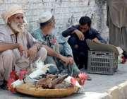 پشاور:  باچا خان چوک کے قریب جمعہ بازار میں ایک بوڑھا شخص دیسی مرغی بیچ ..