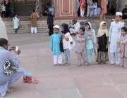 لاہور: بادشاہی مسجد کے احاطے میں ایک شہری موبائل پر بچوں کی تصویر بنا ..