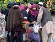 راولپنڈی: موسم سرد ہونے پر طالبات ریڑھی بان سے گرم چھلیاں خریدرہی ہیں۔