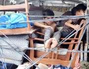 لاہور: تین بچے پک اپ میں سامان کے ہمراہ سفر کر رہے ہیں۔