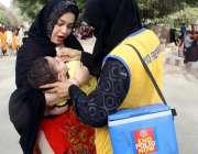 کراچی: لیڈی ہیلتھ ورکر کراچی چڑیا گھرمیں ایک بچے کو پولیو کے قطرے پلا ..