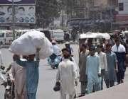 لاہور: ایک شخص بھاری سامان اٹھائے جا رہا ہے۔
