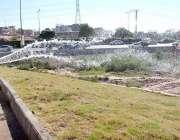 اسلام آباد: س سی ڈی اے اہلکار سڑک کنارے لگے گھاس اور پودوں کو پانی دے ..