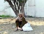 لاہور:خواتین کے عالمی دن کے بے خبر ایک بزرگ خاتون درخت کے سائے میں بیٹھی ..