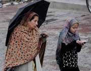 اسلام آباد: بارش سے بچنے کے لیے خاتون نے چھتری تان رکھی ہے۔
