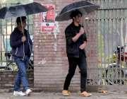 راولپنڈی: شہر میں ہونے والی بارش سے بچنے کے لیے شہریوں نے چھتری تان ..