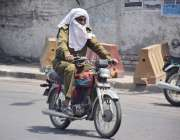 لاہور: موٹر سائیکل سوار پولیس اہلکار گرمی کی شدت سے بچنے کے لیے منہ ..