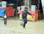 ڈیرہ اللہ یار: ایک بچہ بارش کے دوران گیس کا سلنڈر اٹھائے جا رہا ہے۔