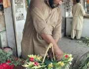 لاہور: سگیاں روڈ پر واقع پھول منڈی میں ایک کاریگر گلدستہ تیار کررہا ..