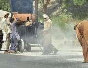 اسلام آباد: وفاقی دارالحکومت میں مزدور سڑک کے تعمیراتی کام میں مصروف ..