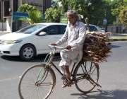 فیصل آباد: ایک معمر شحص سائیکل پر لکڑیاں لادھے اپنی منزل کی جانب رواں ..