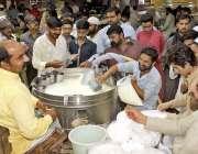 لاہور: شہری ایک دکان سے لسی خرید رہے ہیں۔