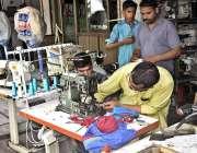 فیصل آباد: مکینک ایمبرائیڈری مشینن کو مرمت کر رہا ہے۔