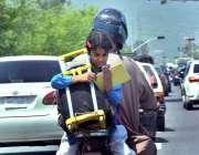 اسلام آباد: وفاقی دارالحکومت میں موٹر سائیکل پر سوار ایک بچی بیگ اٹھائے ..