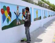 فیصل آباد: عید الفطر کی آمد کے موقع پر ایک آرٹسٹ دیوار پر کارٹون بنا ..