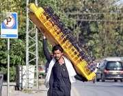 راولپنڈی: محنت کش دھوپ سے بچاؤ والی عینکیں فروخت کے لیے اٹھائے لیجا ..