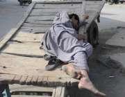 راولپنڈی: کام کے انتظار میں ایک مزدور اپنے ریڑھے پر سو رہا ہے۔