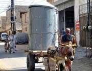 بہاولپور: ایک شخص سڑک پر کنٹینر سے لدے اپنے گدھا گاڑی کے ساتھ چل رہا ..