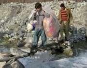 گلگت: ایک شخص اپنے بچے کے ہمراہ سامان اٹھائے دریا کا پل کراس کررہا ہے۔