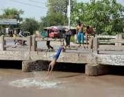 فیصل آباد: نوجوان گرمی کی شدت کم کرنے کے لیے نہر میں نہا رہے ہیں۔