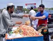 سیالکوٹ: موٹر سائیکل سوار ریڑھی بان سے گنڈیریاں خرید رہا ہے۔