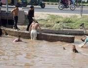 لاہور: نوجوان گرمی کی شدت کم کرنے کے لیے نہر میں نہا رہے ہیں۔