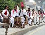 راولپنڈی: سڑک کے کنارے بیٹھے ہوئے روایتی ڈھول بجانے والے بیٹھے ہیں۔