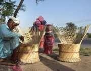 لاہور: محنت کش روایتی انداز سے (کانے) کی کرسیاں بنا رہا ہے۔