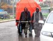 راولپنڈی:بارش کے دوران کام میں مصروف مزدوروں نے سامان کوشیٹ سے ڈھانپ ..