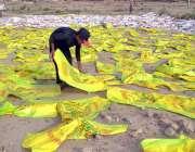 ملتان: مزدور پلاسٹک بیگز خشک کرنے کے لیے دھوپ میں پھیلا رہاہے۔