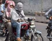 لاہور: موٹر سائیکل سوار شہری گرمی کی شدت سے بچنے کے لیے منہ کو کپڑے سے ..