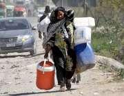 راولپنڈی: ایک خاتون خالی کین اٹھائے پینے کے لیے پانی بھرنے جارہی ہے۔