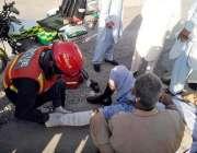 راولپنڈی: ریسکیو اہلکار ٹریفک حادثہ سے زخمی شخص کو فرسٹ ایڈ دے رہا ہے۔