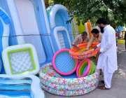 پشاور: سڑک کنارے لگے سٹال سے شہری بچوں سوئمنگ پول پسند کر رہا ہے۔