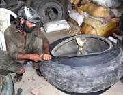 لاڑکانہ: مزدور ٹائروں کے دکان پر اپنے روزہ مرہ کام میں مصروف ہے۔