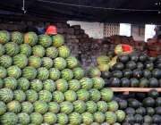راولپنڈی: راجہ بازار میں محنت کش نے تربوز فروخت کے لیے سجا رکھے ہیں۔
