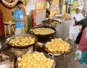 لاہور: دکاندار گاہکوں کو متوجہ کرنے کے لیے سموسے فرائی کر رہا ہے۔