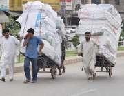 لاہور: محنت کش ہتھ ریڑھیوں پر بھاری سامان رکھے جا رہے ہیں۔