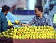 راولپنڈی: شہری سڑک کنارے ریڑھی بان سے آم خرید رہاہے۔