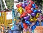 راولپنڈی: محنت کش غبارے فروخت کرنے کیلئے ہوا بھرنے میں مصروف ہے۔