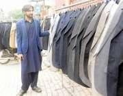 راولپنڈی: ہفتہ وار بازار میں ایک دکاندارکوٹ فروخت کیلئے سجارہا ہے۔