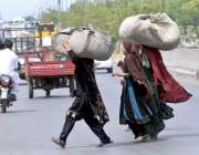 راولپنڈی: خانہ بدوش خواتین سروں پر بھاری گٹھڑیاں اٹھائے جا رہی ہیں۔