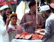 پشاور: شہری ریڑھی بان سے تربوز کھا رہے ہیں۔