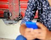 اسلام آباد: نوجوان دکاندار ہڑتال کے باعث بند دکان کے باہر موبائل فون ..