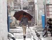اسلام آباد: وفاقی دارالحکومت میں ایک طالبعلم بارش سے بچنے کے لیے چھتری ..